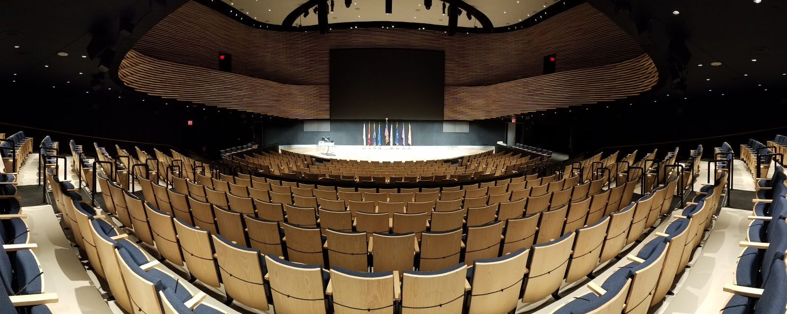 Panorama of KG Tan Auditorium from the students view. There  is a stage with an ADA complaint Teaching station to the left. There is two tiers of seating.