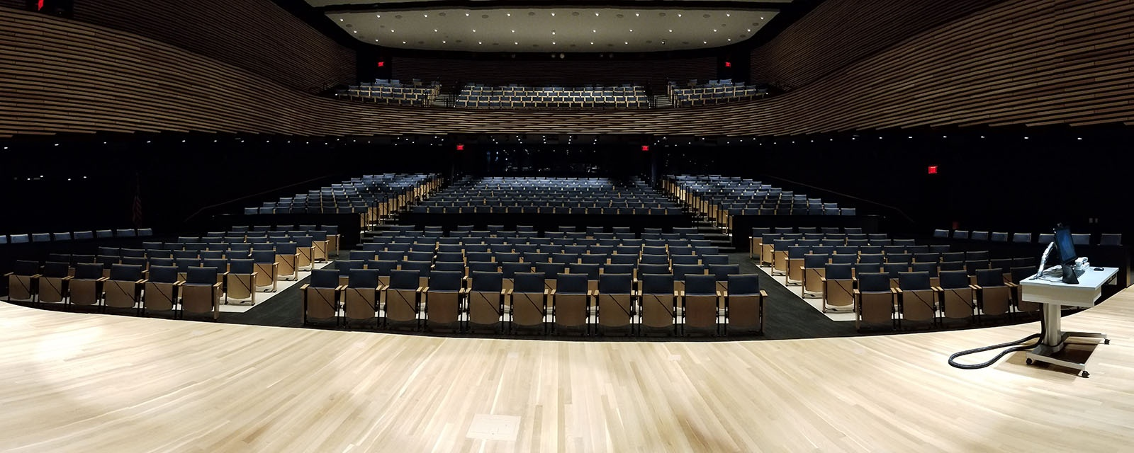 Panorama of KG Tan Auditorium from the teachers view. There  is a stage with an ADA complaint Teaching station to the right. There is two tiers of seating.