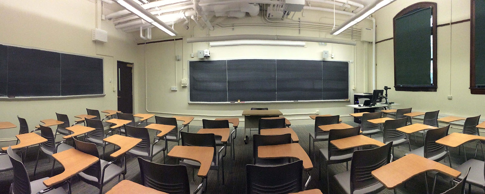 Carnegie 114 panorama from rear to front, chairs moveable with desk attached, teaching station to left of entrance