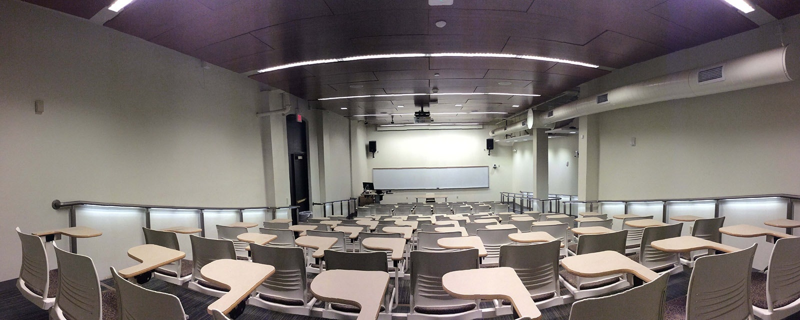 Panorama of Carnegie 122 from rear to front, chairs stationary with desk attached, teaching station at front, left of entrance