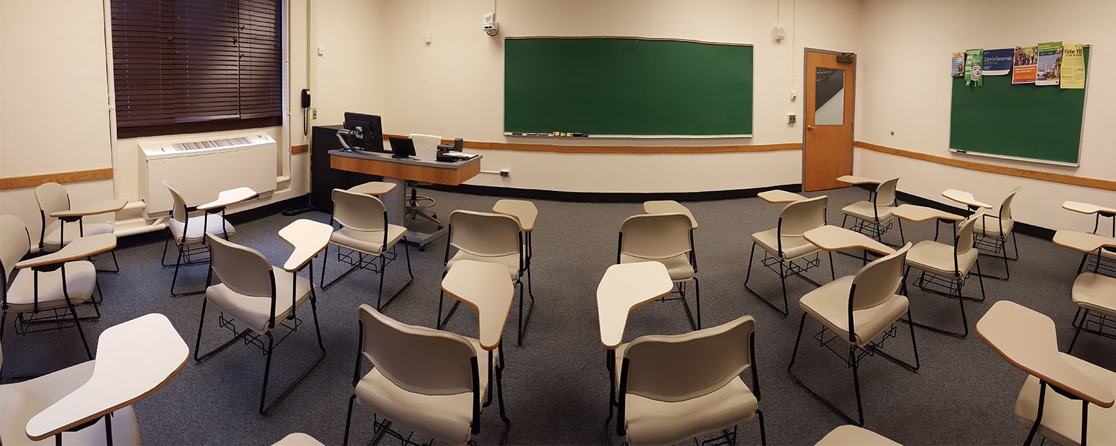 Panorama Bowne 108 from back of room to front of room, chairs moveable with desks attached, teaching station directly across from door.