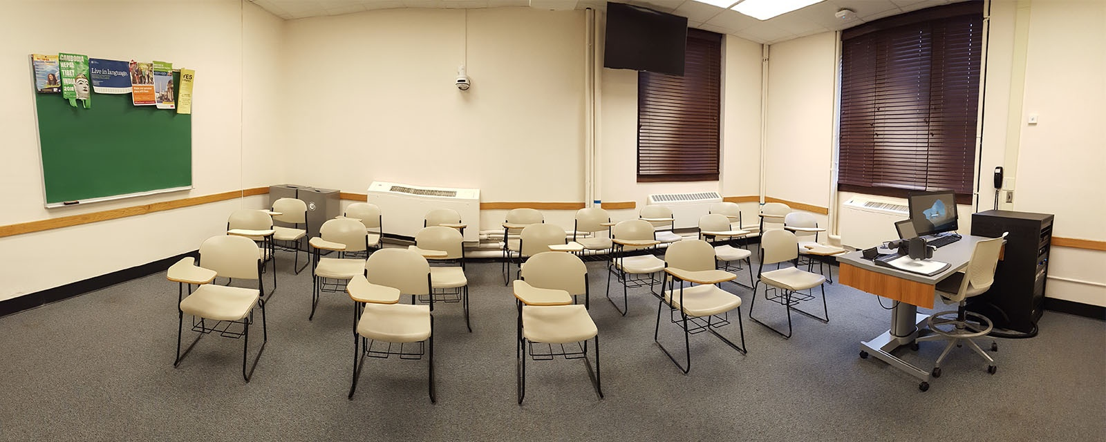 Panorama Bowne 108 from front of room to back of room, chairs moveable with desks attached, teaching station directly across from door.