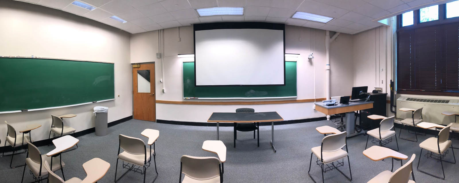 Panorama Bowne 110 from back of room to front of room, chairs moveable with desk attached, teaching station on left side of room after entering.