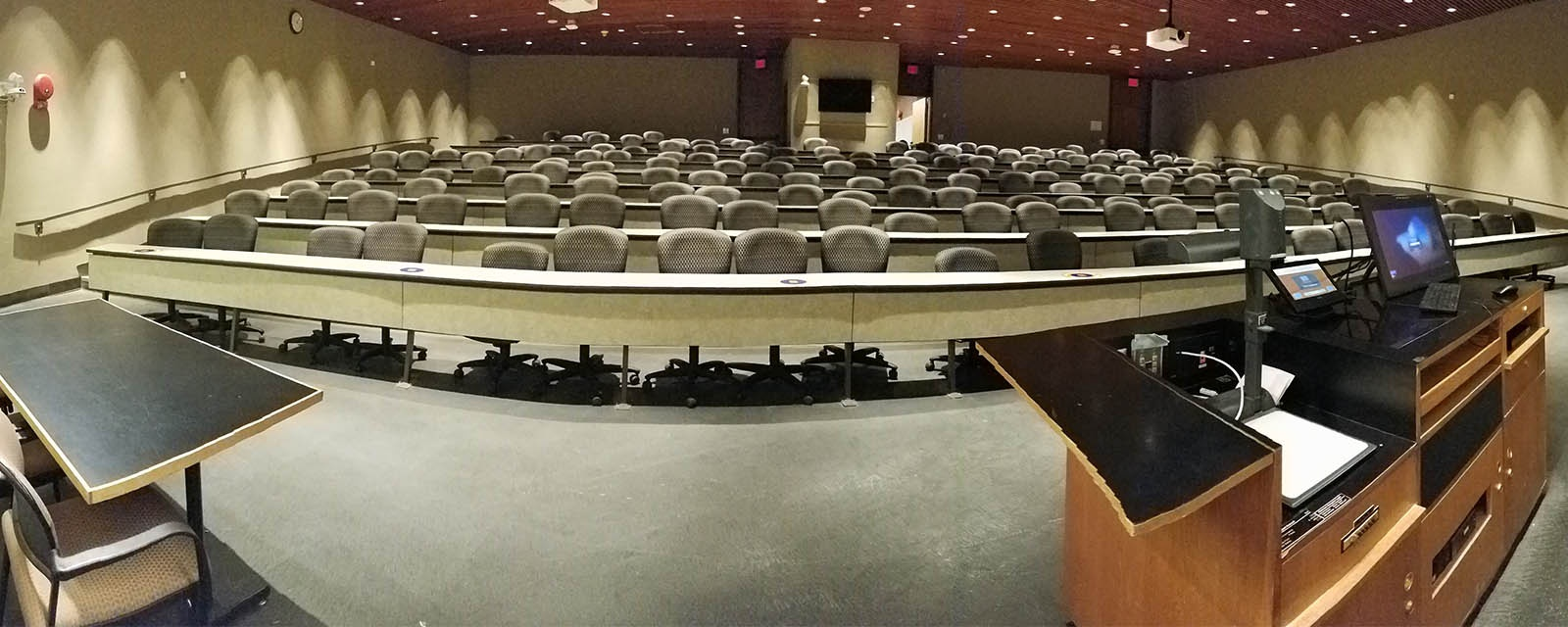 Panorama Heroy auditorium from front of room to back of room, stadium seating with tables, teaching station front center