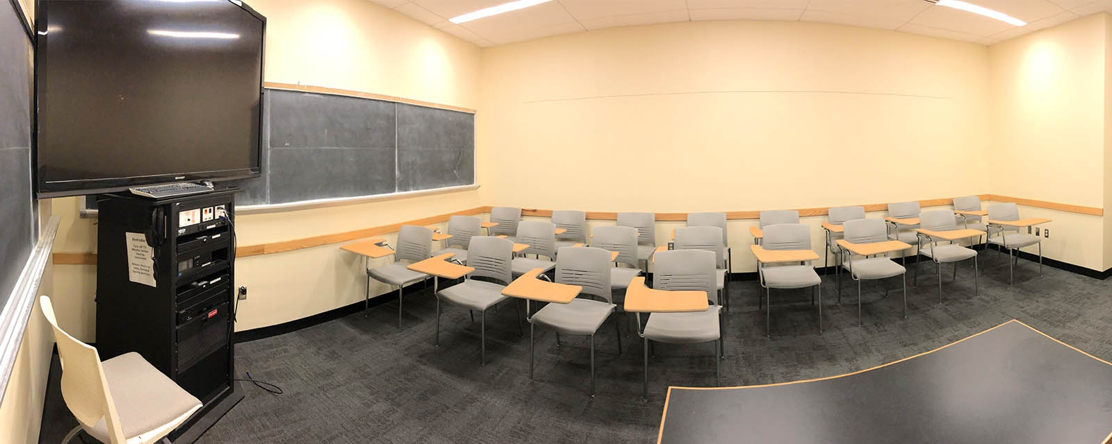 Panorama of HBC 306 from front of room, moveable chairs, teaching station front left