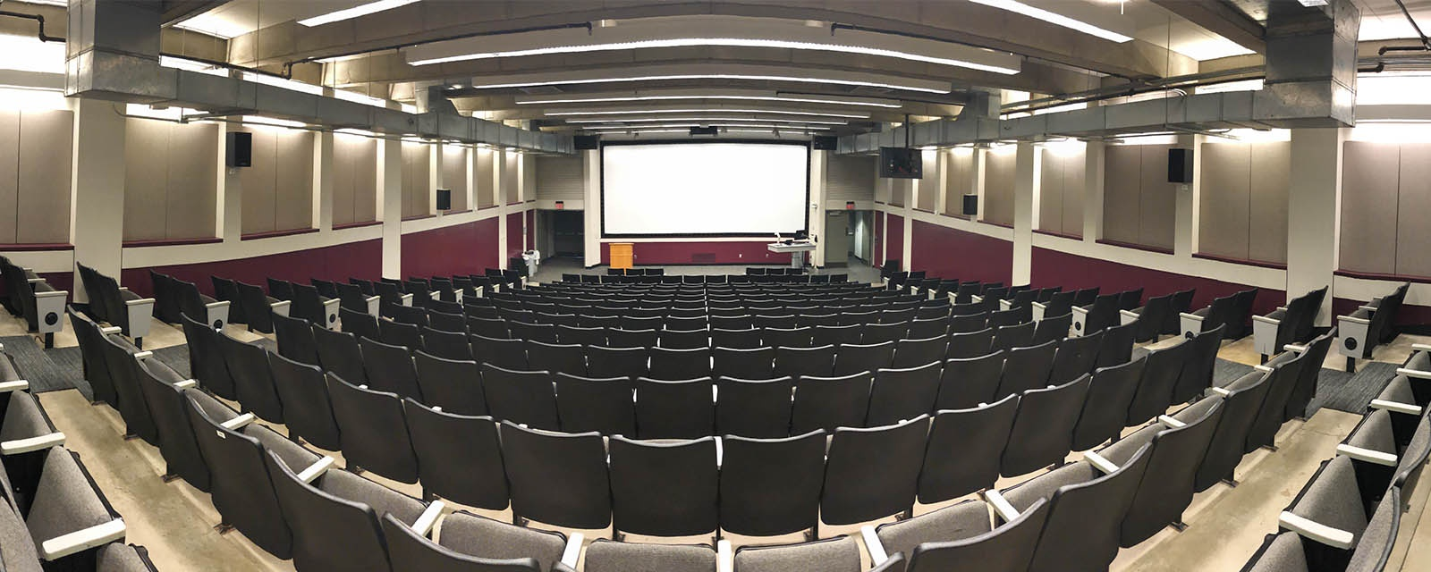 Panorama Shaffer Shemin Auditorium from back, stadium seating, teaching station front left of room to front of room