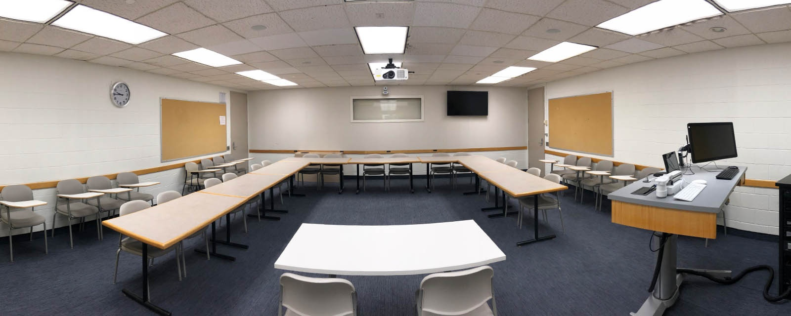 Panorama of N2 340 from the front of the classroom, teaching station and als on the right, chairs and tables in the center of the room.