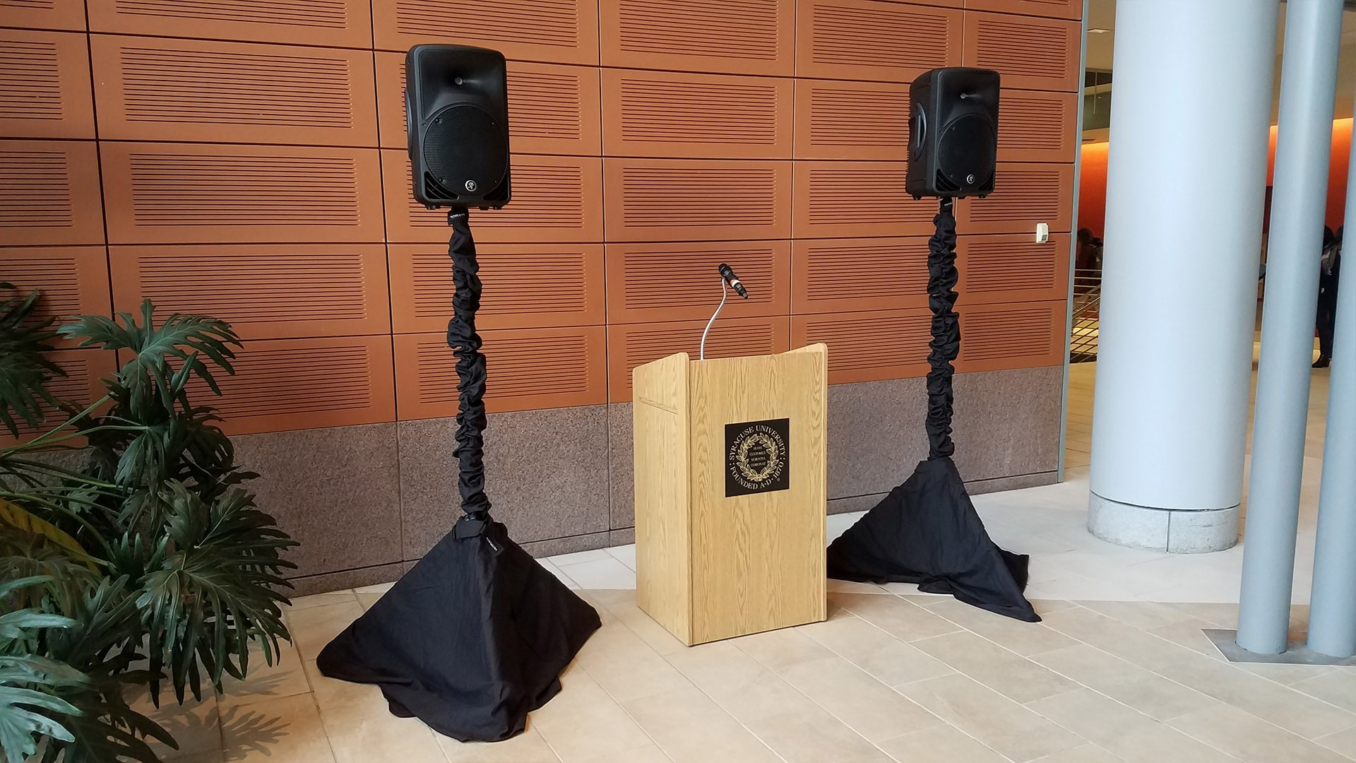 Public Address System with 2 speakers on stands and a podium with a wireless microphone attached