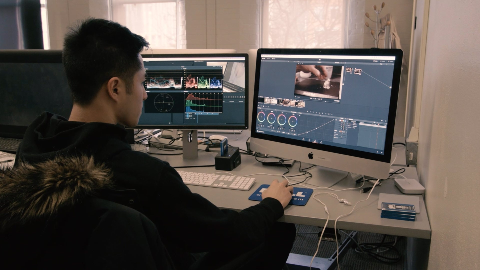 student employee working on computer video editing