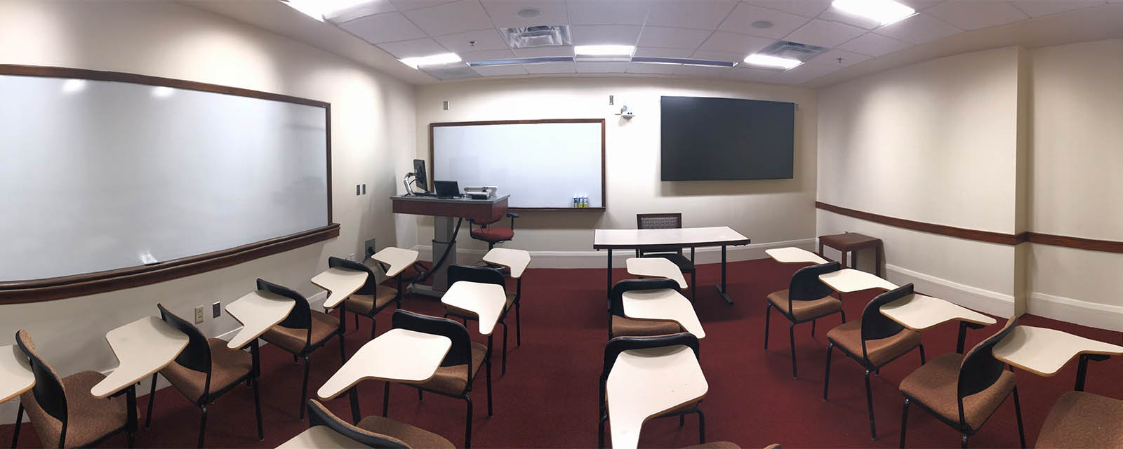 Panorama of Tolley 115 from the rear of the room to the front. The chairs are movable and in rows. The teaching station is fixed and located in the audience's front left of the room.