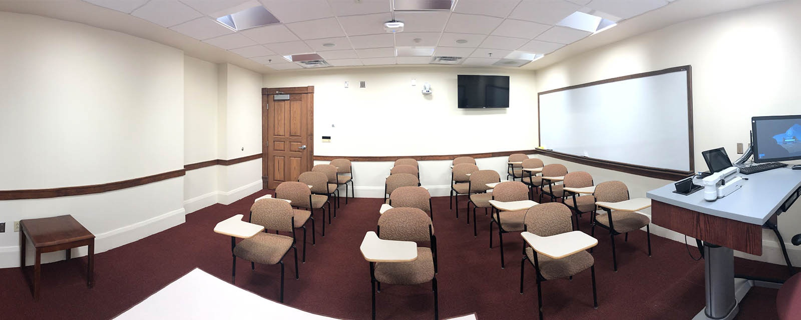 Panorama of Tolley 115 from the front of the room to the rear. The chairs are movable and in rows. The teaching station is fixed and located in the audience's front left of the room.