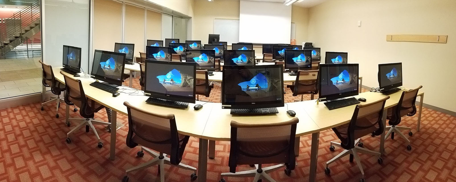 Panorama of room from students perspective. Fixed Teaching Station on left. 4 rows of computers with mobile chairs.