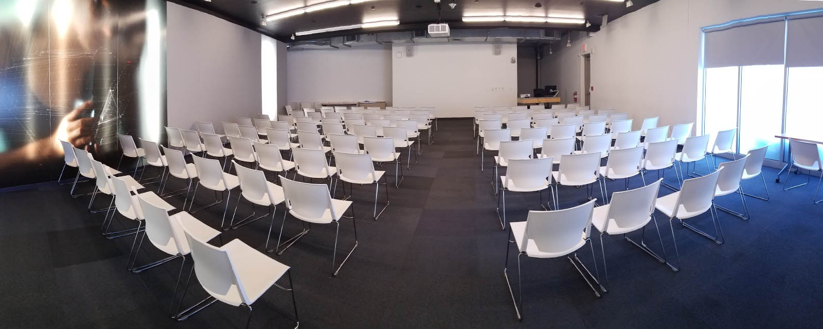 Panorama of Warehouse 100A from the  back of the room, teaching station on the right, moveable tables and chairs in the center of the classroom.