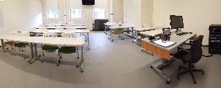 Panorama of Smith 227 from front of room, moveable chairs, teaching station front right